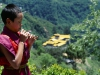 Young Monk blowing reed flute, Tongsa Dzong behind