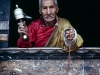 Tibetan shopkeeper with prayer wheel; Paro